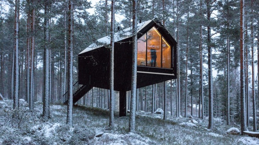 A black-painted cabin elevated in woodland in Finland