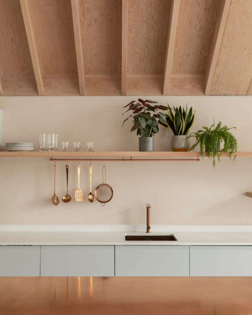 A pastel-hued kitchen with an exposed timber ceiling