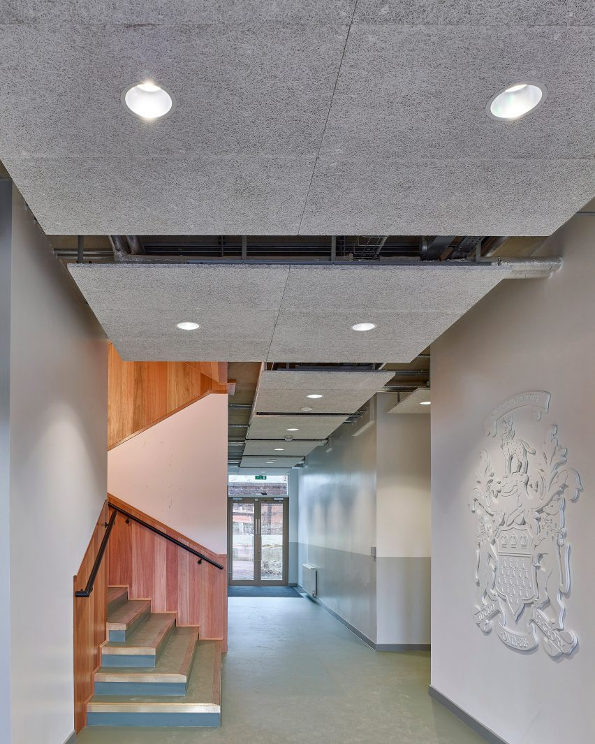 White walls with school crest next to timber lined stairwell