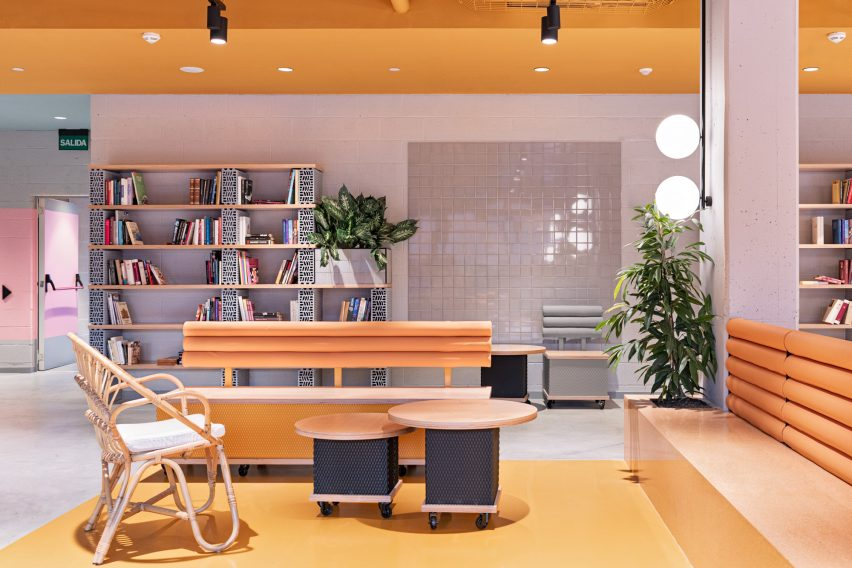 Yellow lounge space with wooden furniture by Masquespacio