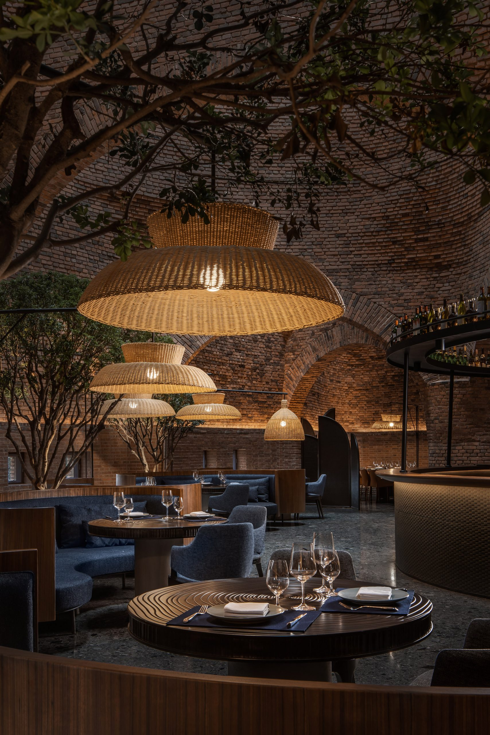 A restaurant with red-brick walls and woven lampshades