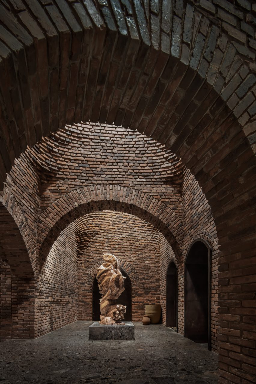 A sculpture within an arched-brick corridor