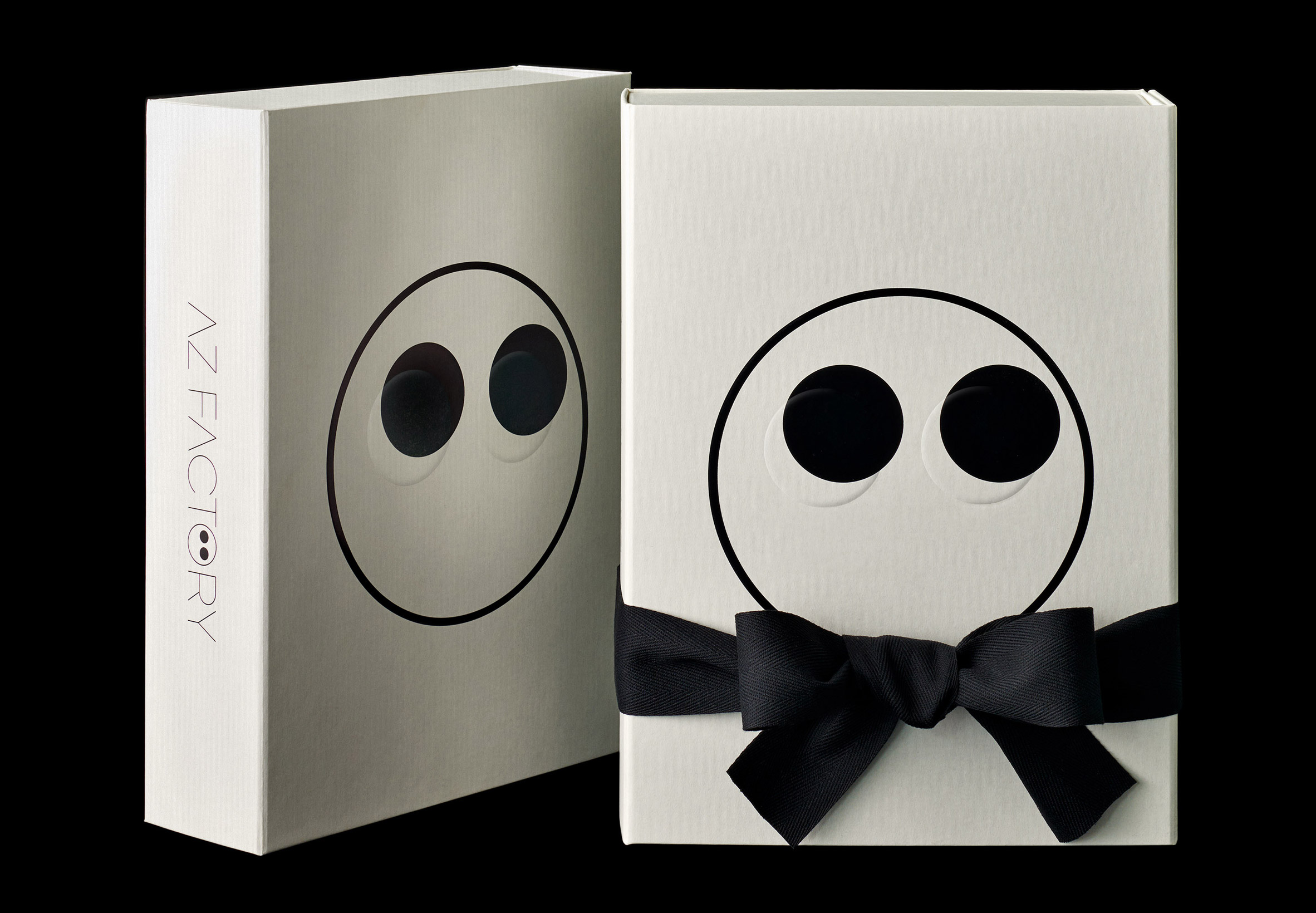 AZ Factory packaging with bow tie and an embossed face motif