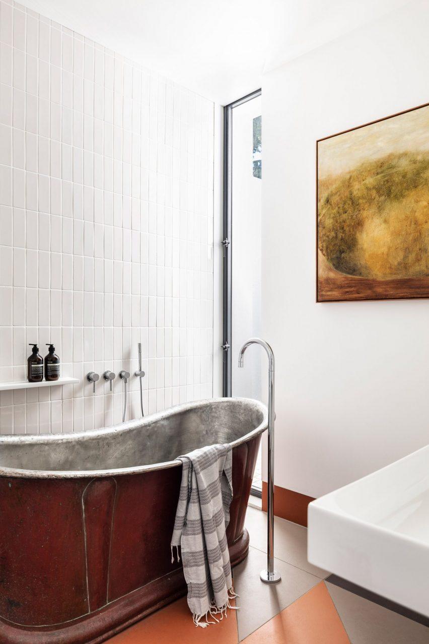 Metal bath in tiled bathroom