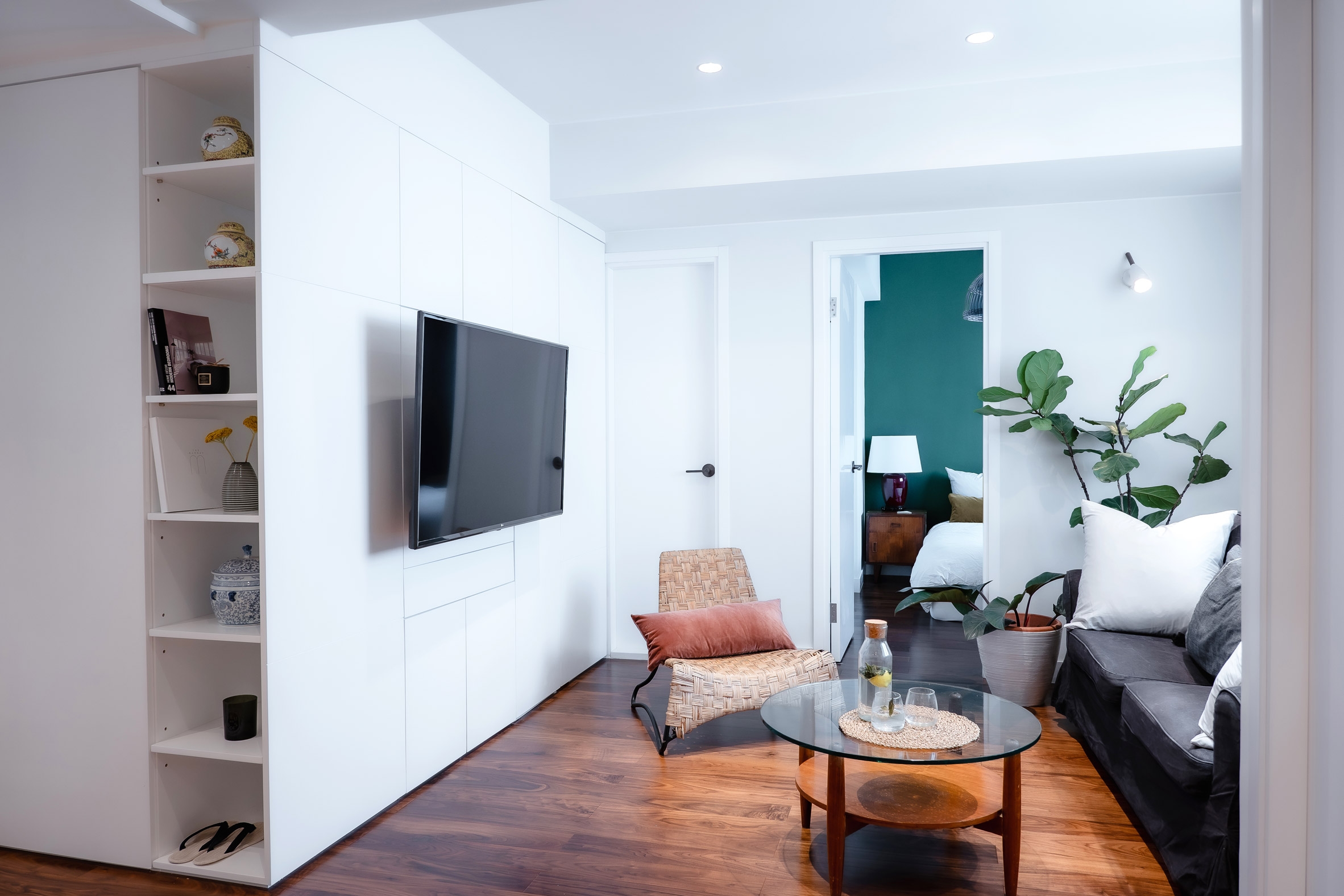 Wooden floors in white flat with green accent wall