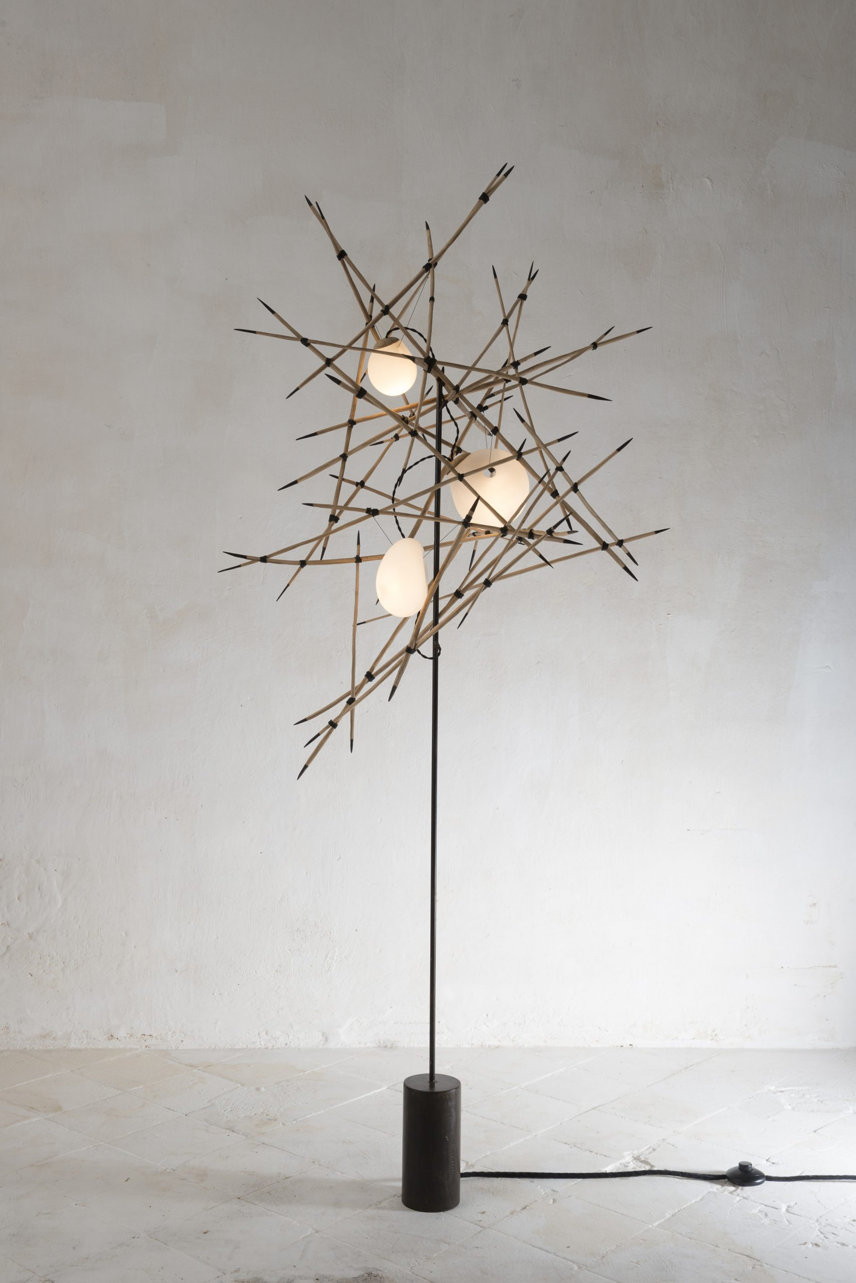 A floor lamp that looks like handfuls of matchsticks