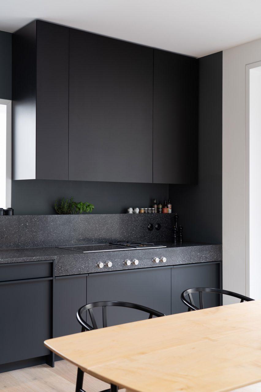 Dark grey kitchen contrasts against the light interior