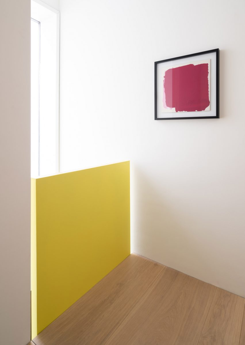 Yellow balustrade contrasts against wood floor and white walls