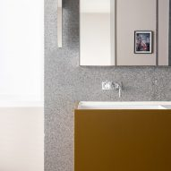 Walls are clad with grey terrazzo