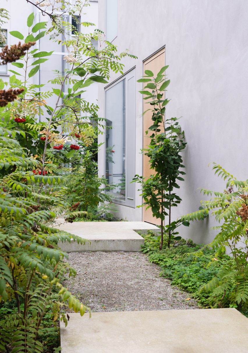 Greenery surrounds the paths into the home
