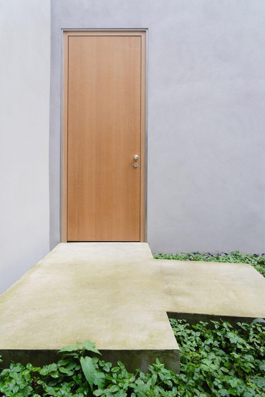 A wooden door is flush against the exterior walls by Batek Architekten