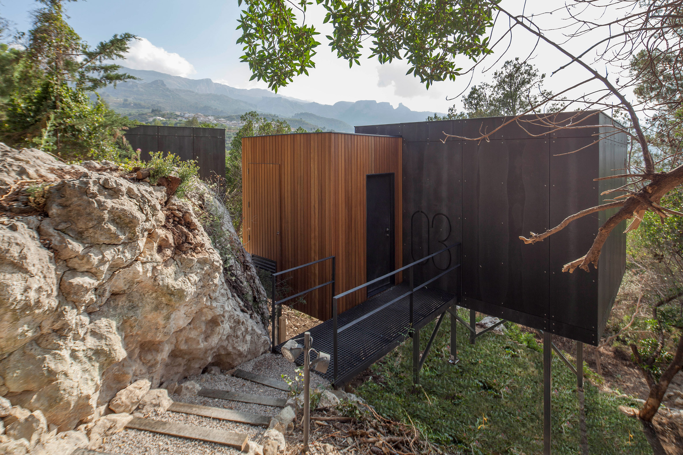 Cabin on stilts accessed by a path along a rocky terrain by Daniel Mayo