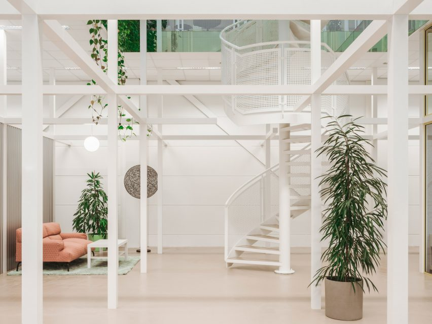 White perforated spiral staircase complements the white framework