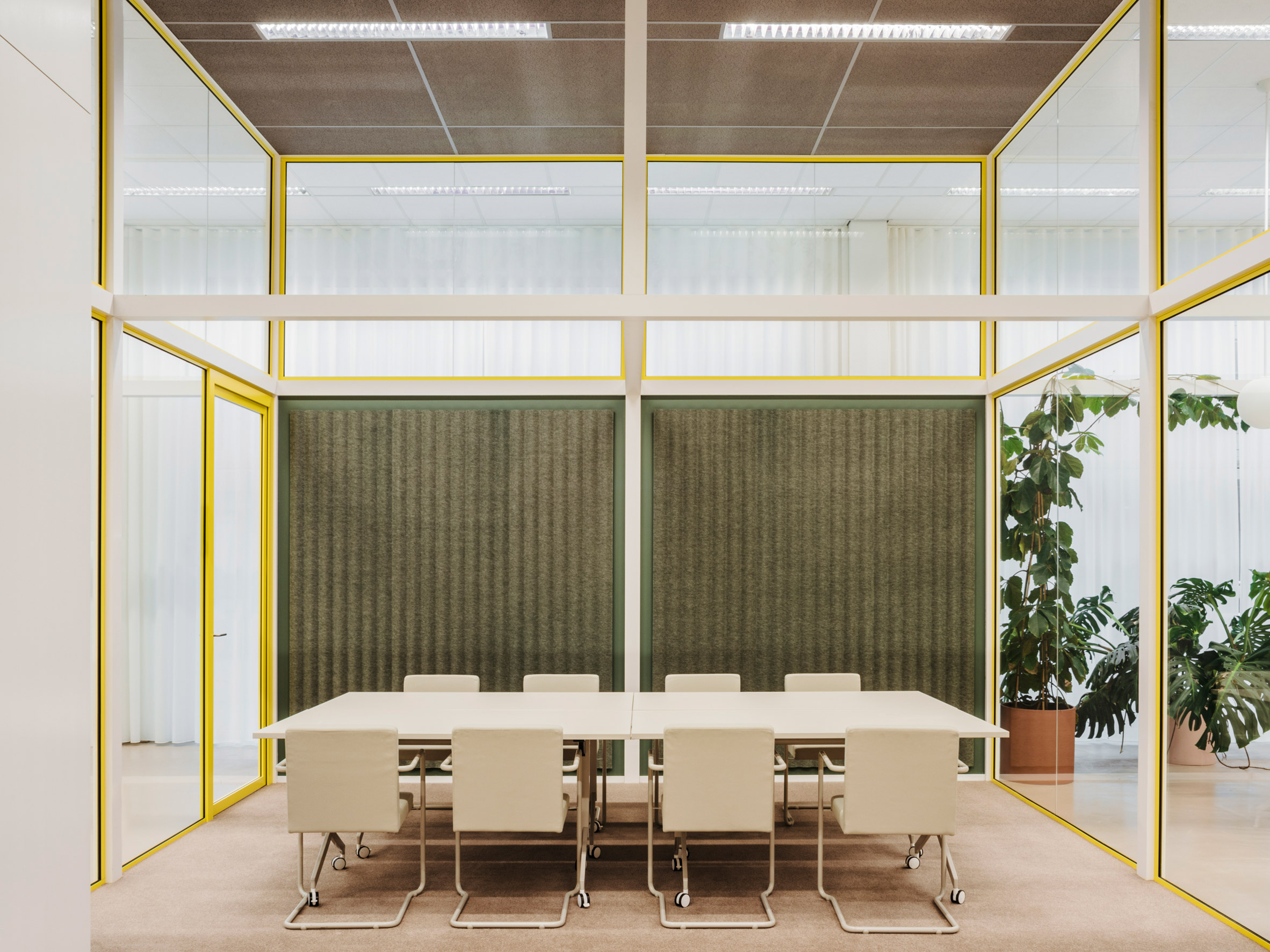 Meeting table in glass room with felt wall