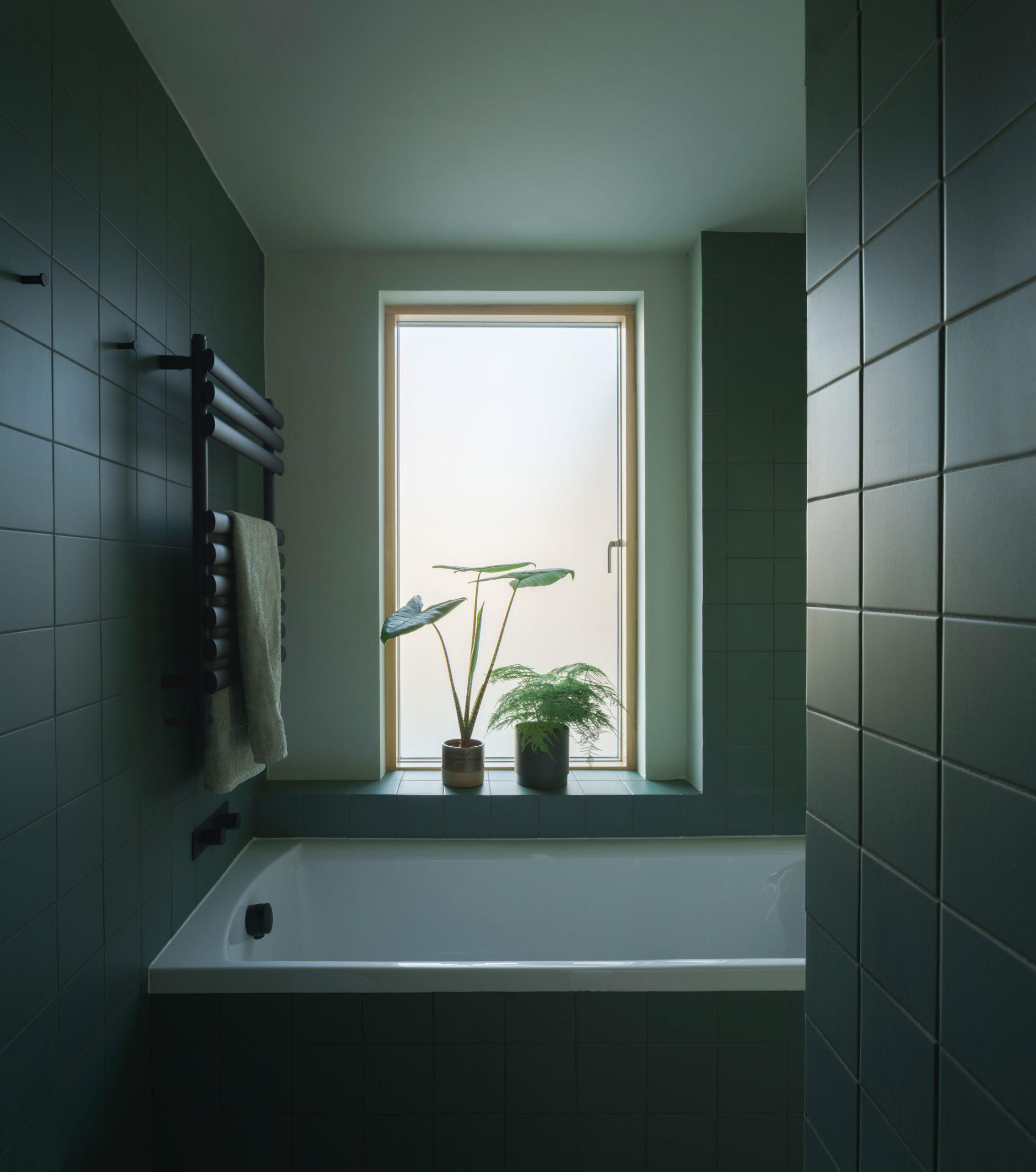 A bathroom lined with matt-green tiles in a terraced London house