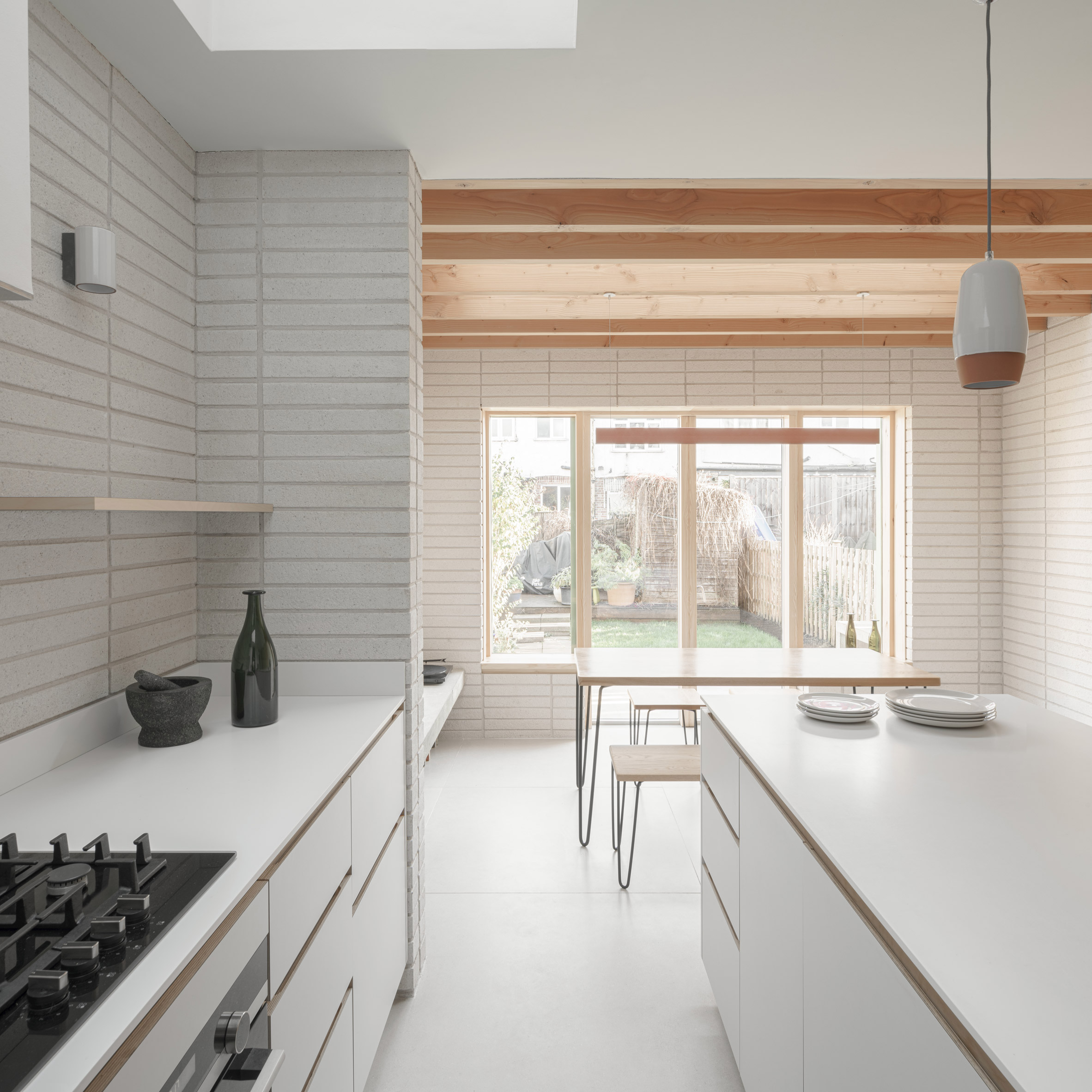 A white kitchen in a London house extension by DeDraft