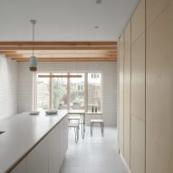 A white and wood-lined kitchen in a London house extension by DeDraft