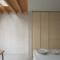 A white and wood-lined kitchen in a house extension in London by DeDraft
