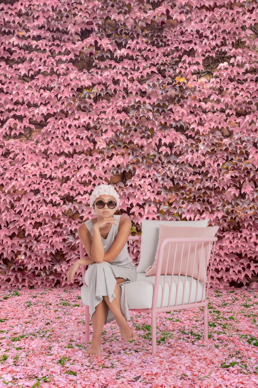 Woman sitting on pink Arp chair in a flower garden