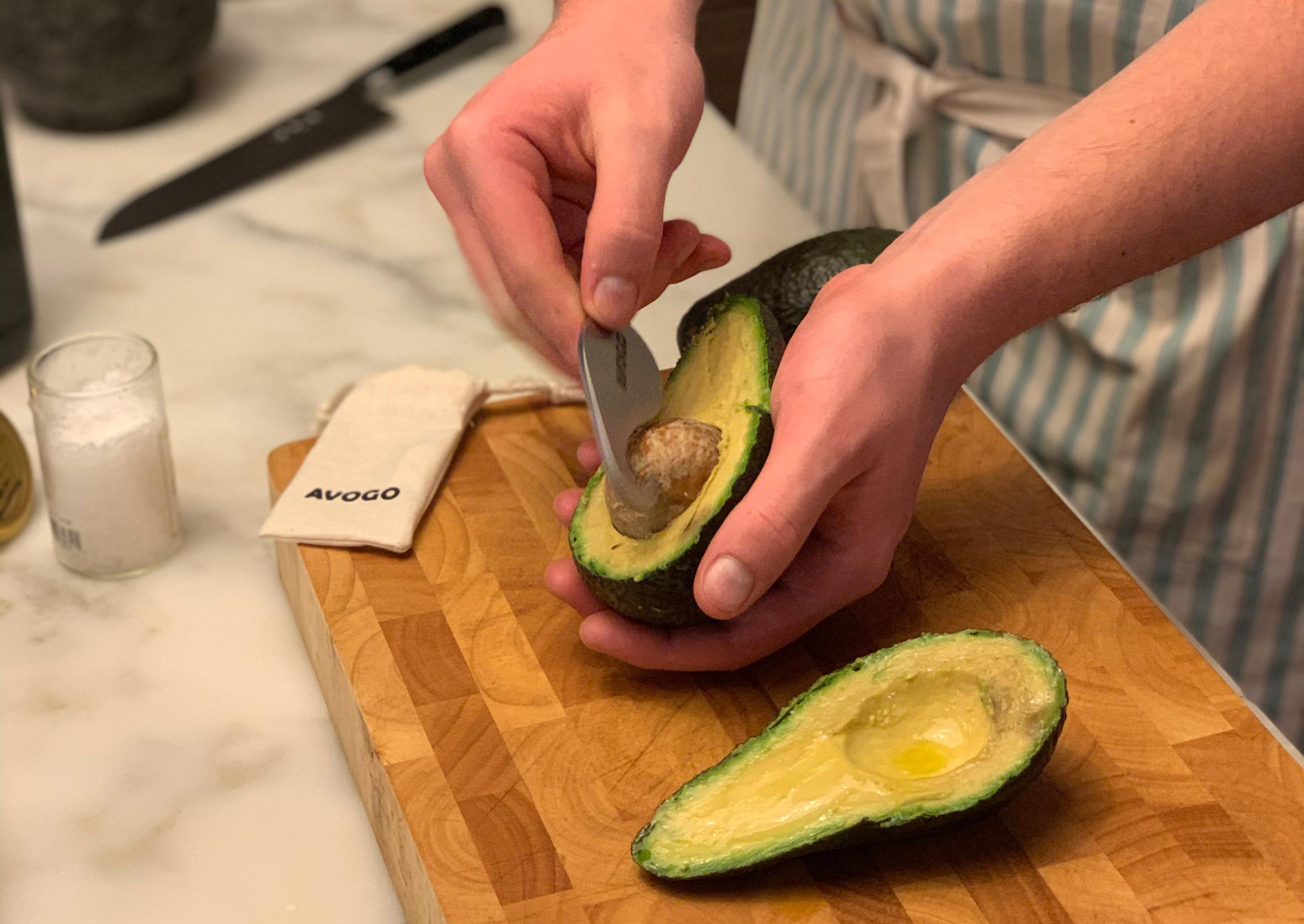 Avogo travel-sized avocado cutter in use