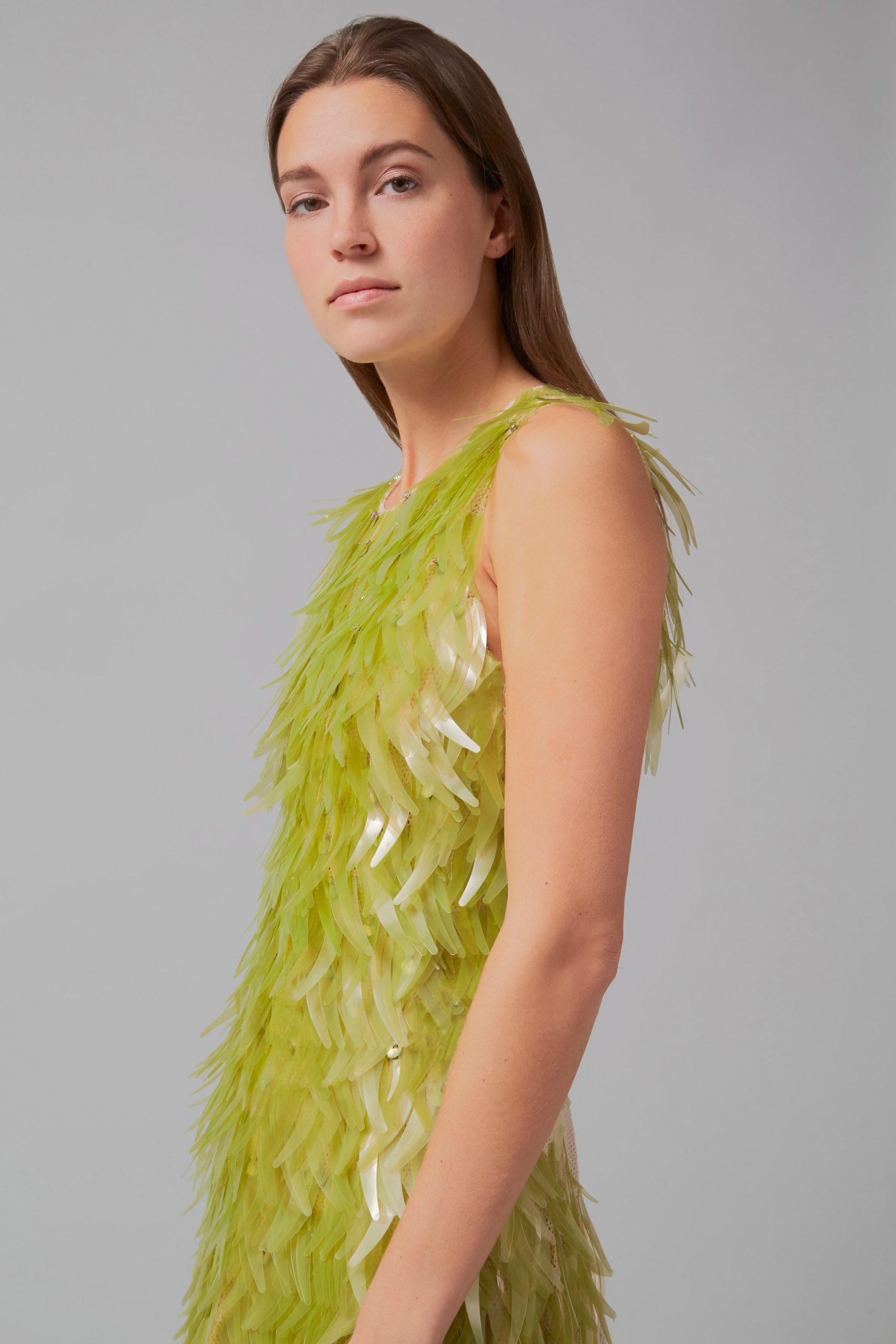 Side profile of algae sequin dress by Phillip Lim as part of One X One project