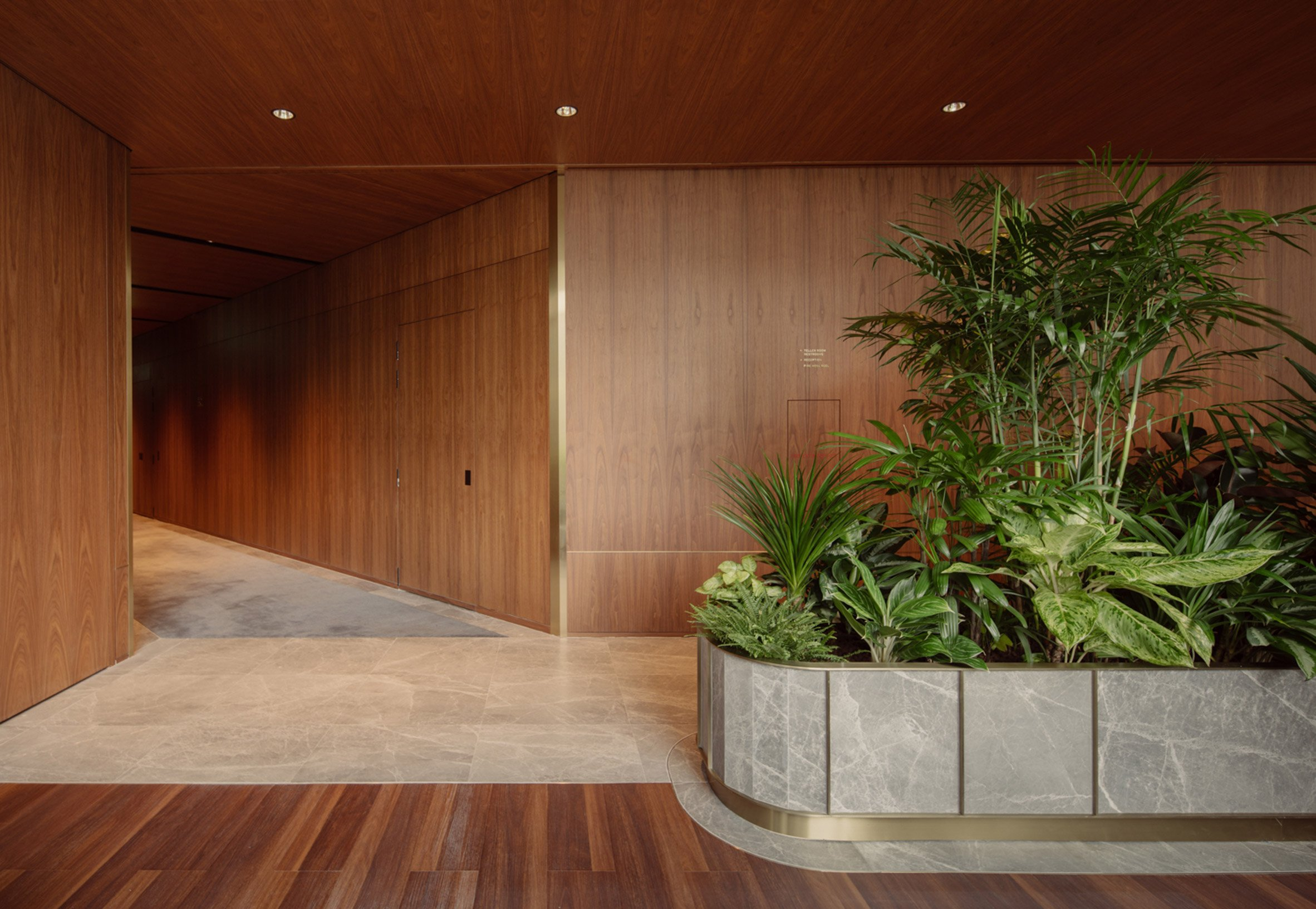 Marble planters and walnut wood walls on level eight of Citi Wealth Hub by Ministry of Design