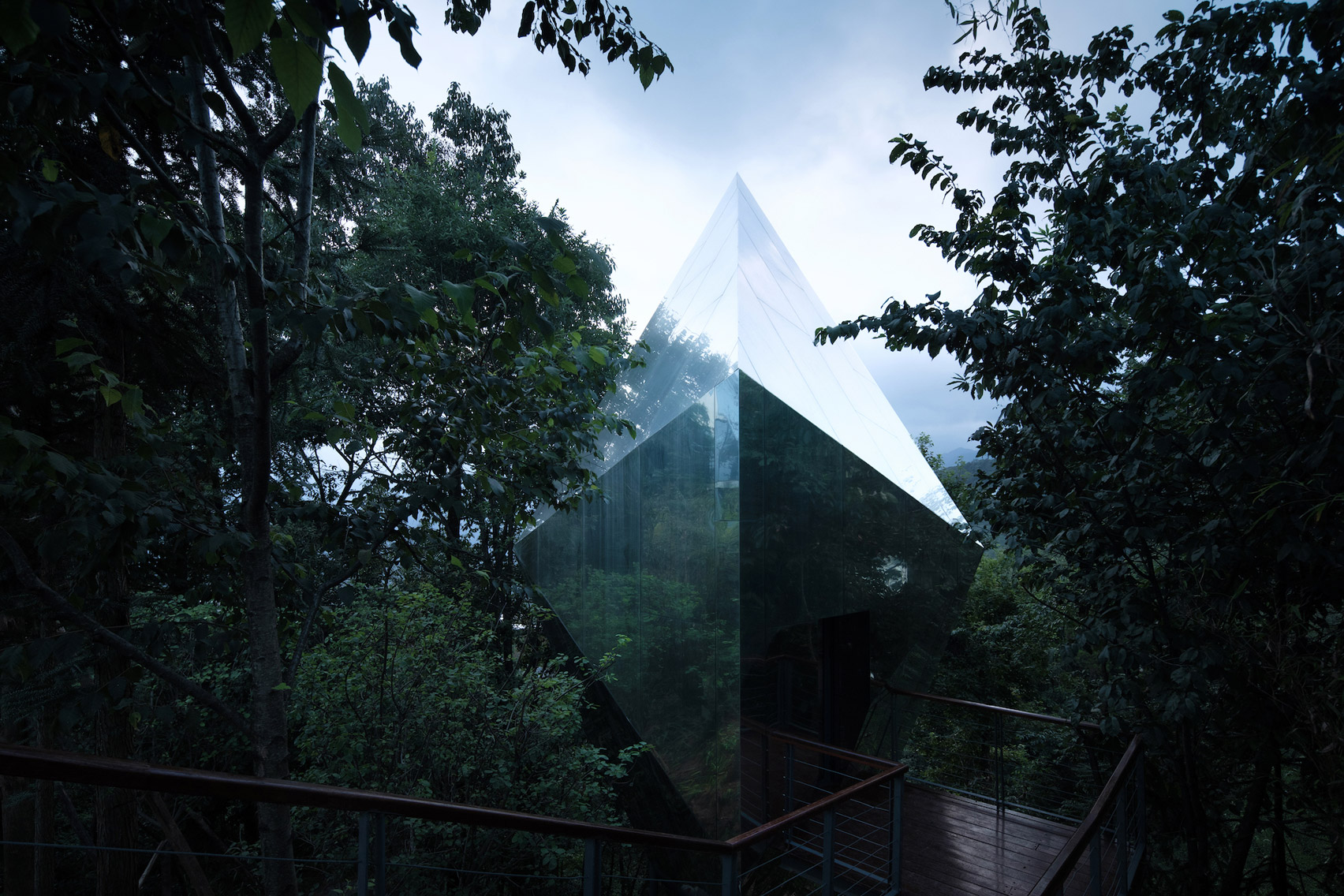 Mirrored cabins sit within the tree-line