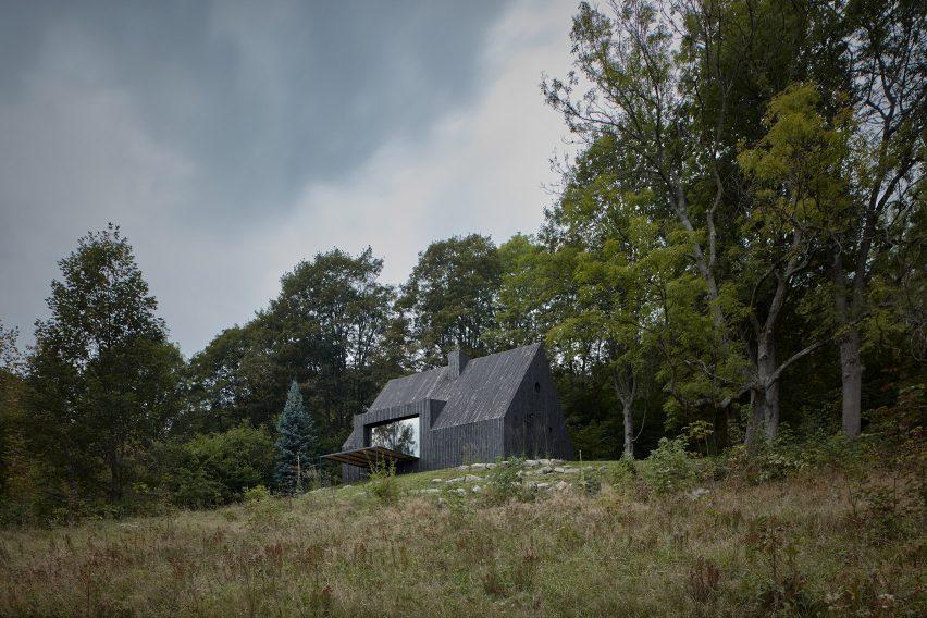Charred wood cottage sits amongst a wooded area by Mjölk Architekti