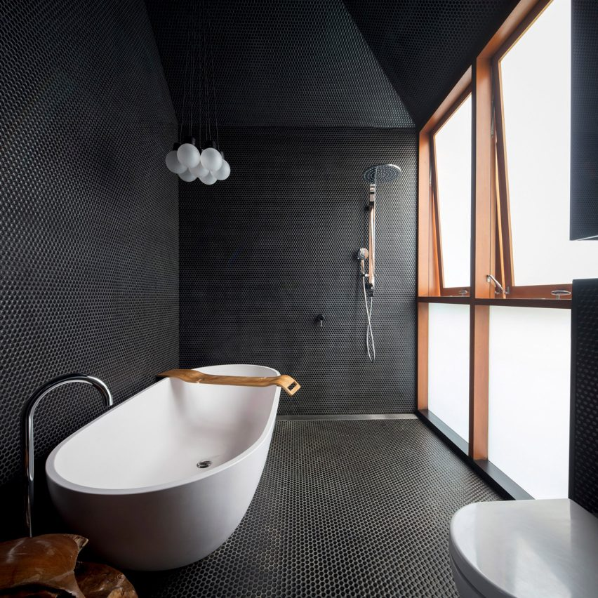 Black-tiled bathroom with freestanding bath