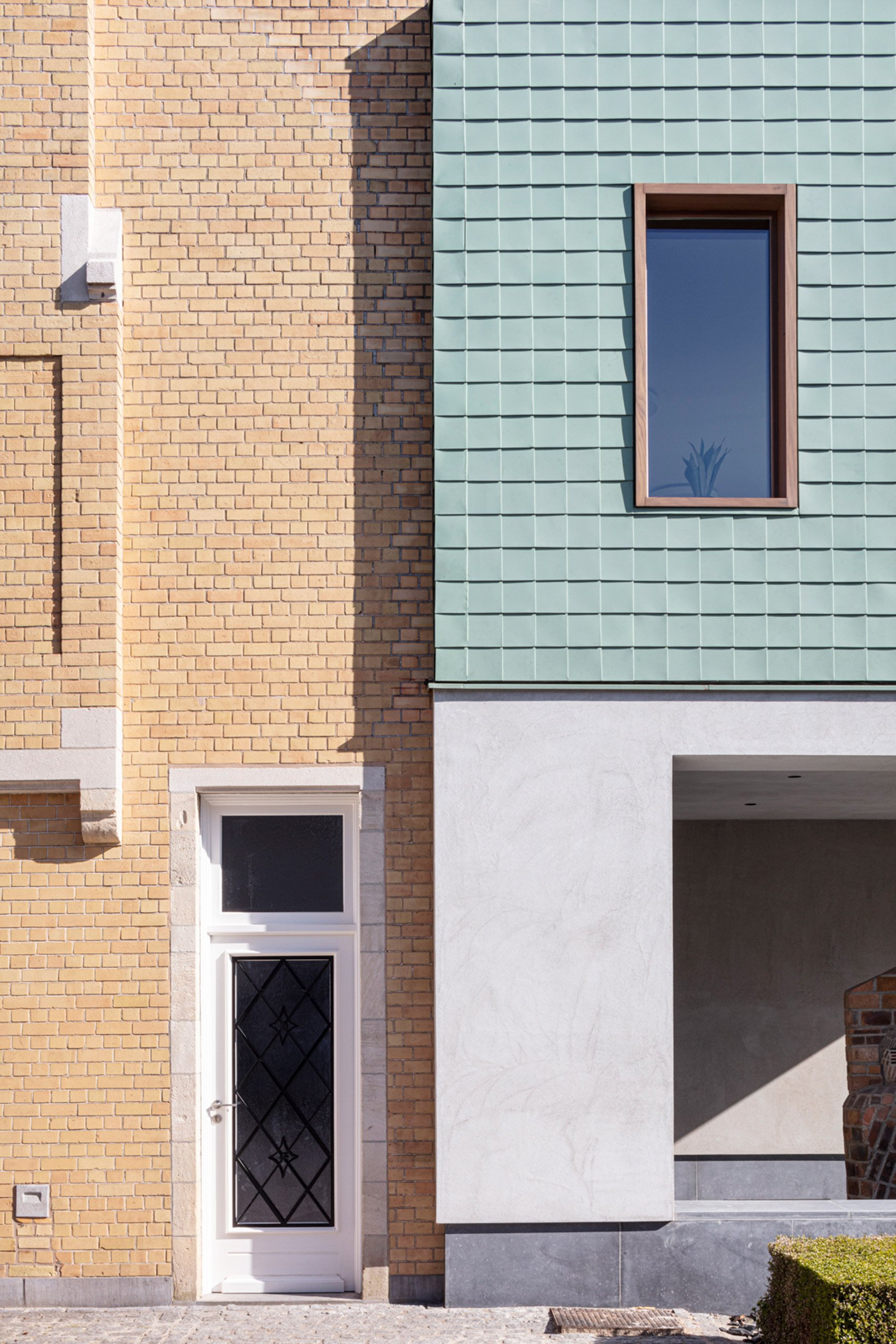 Wood windows are dotted between the cladding