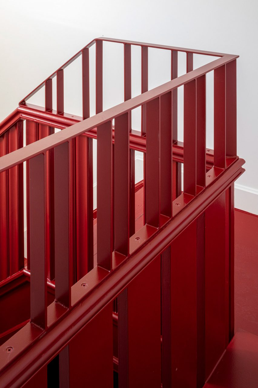 Red painted staircase with a steel and wooden balustrade