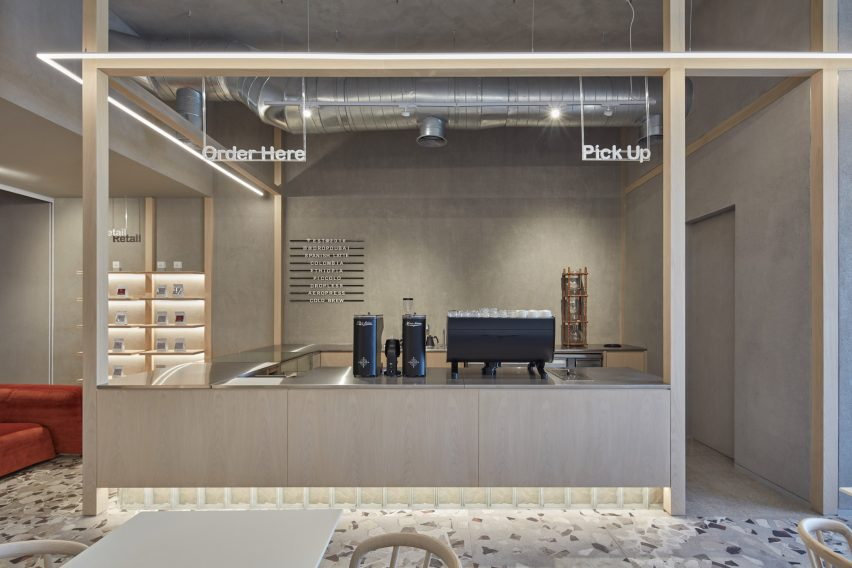 Wooden coffee bar counter with concrete base and floor lighting