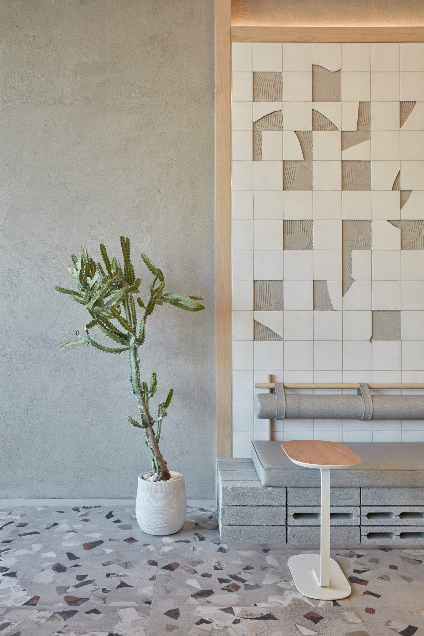 Broken-ceramics wall with green plant and terrazzo floor in Drop Coffee