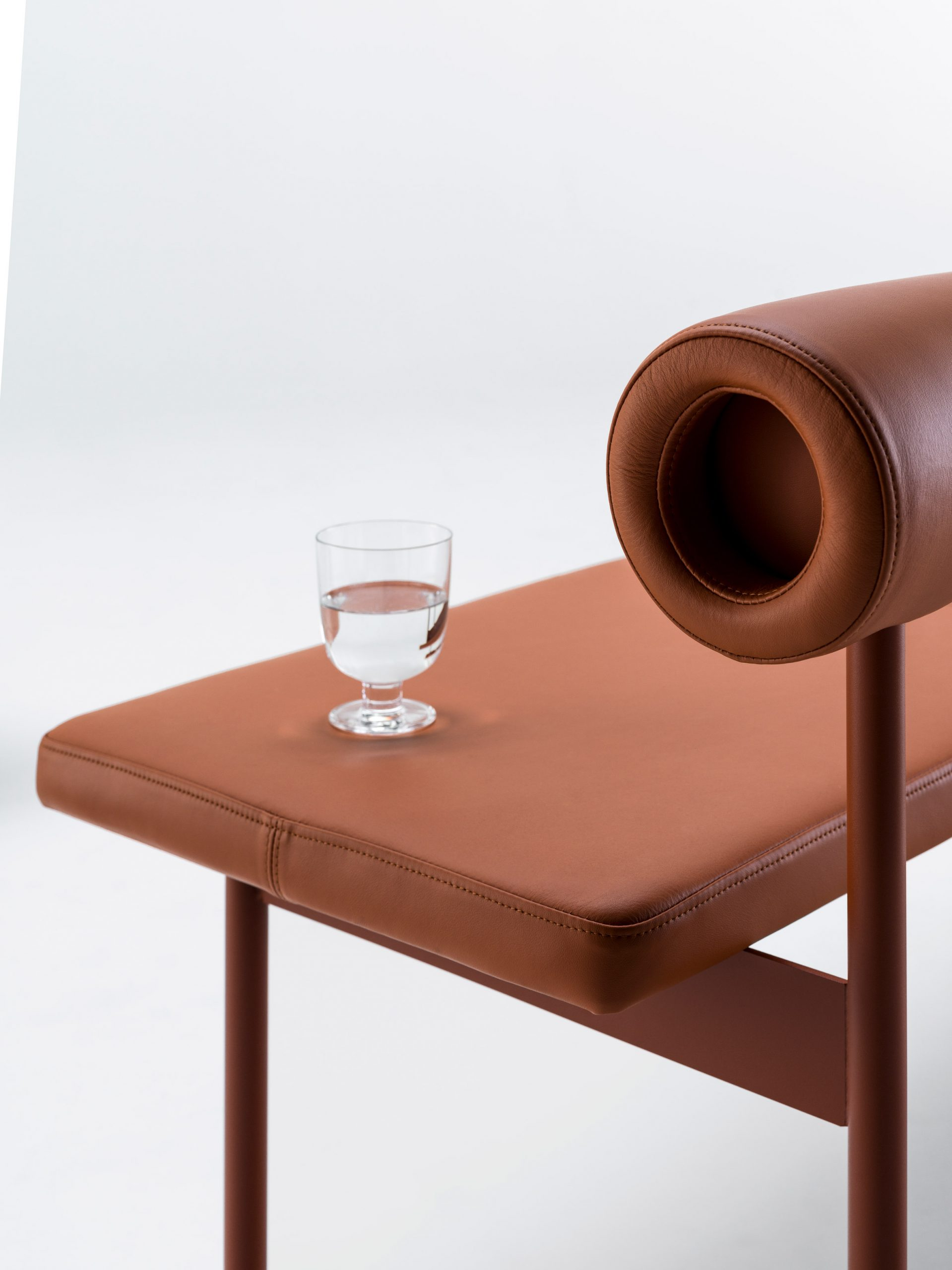 Font sofa in terracotta leather with a glass of water balanced on it