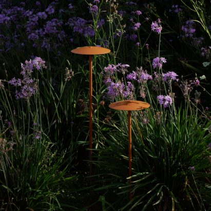 Two outdoor lamps by Marset hidden within greenery