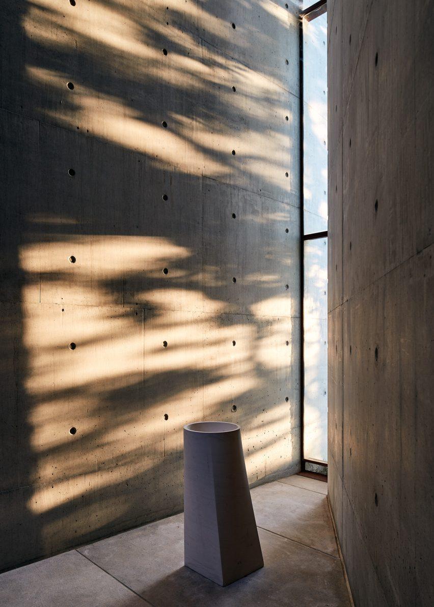 A narrow window lighting a concrete room