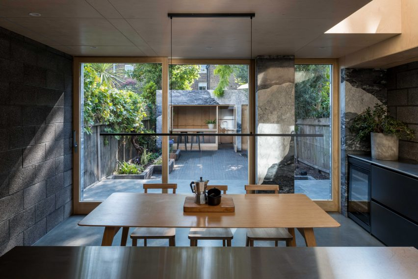 Stainless steel kitchen looking out at garden and marble-clad garden room of Hansler Road extension by Alexander Owen Architecture