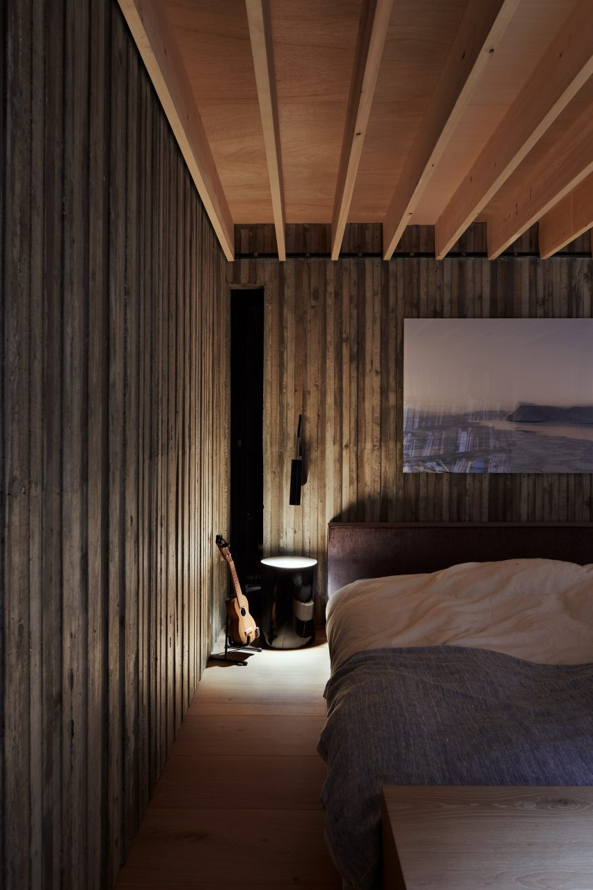A dark timber-lined bedroom
