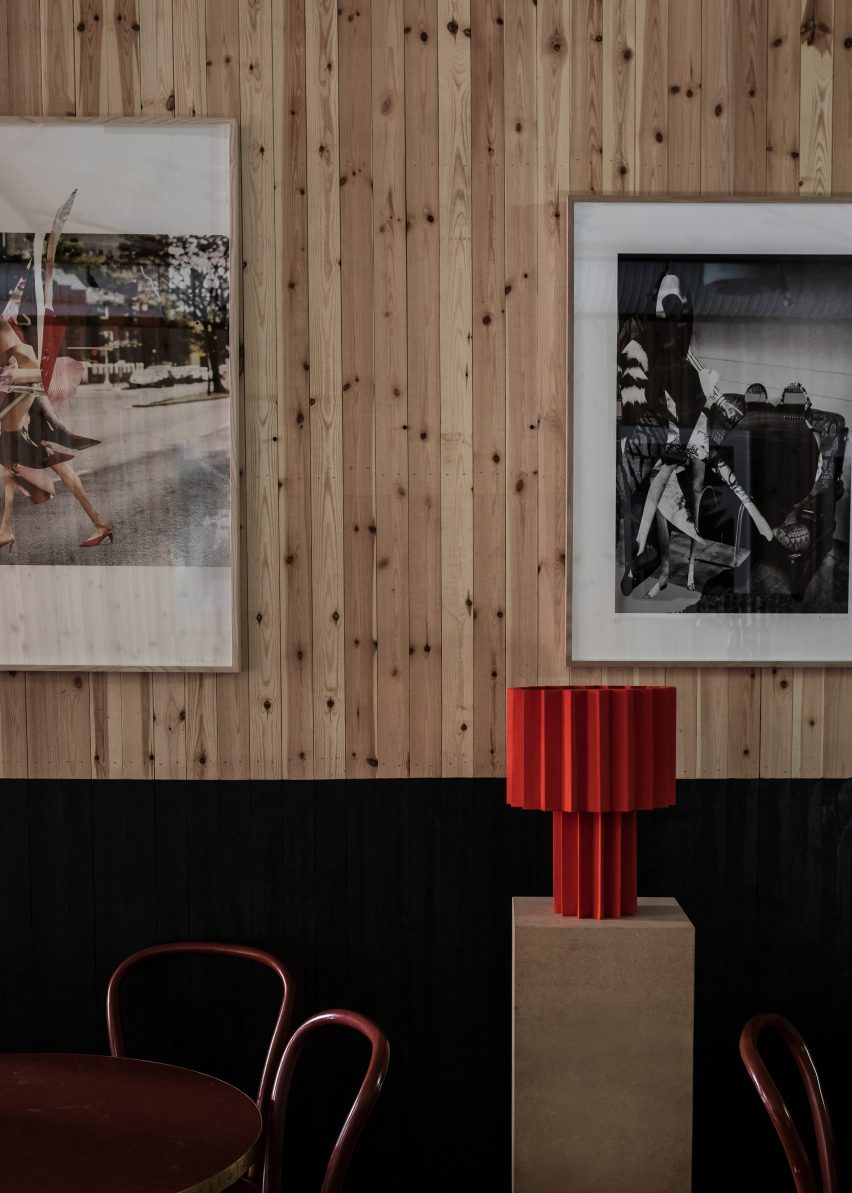 Red pleated lamp and black and white prints by Roland Hjort
