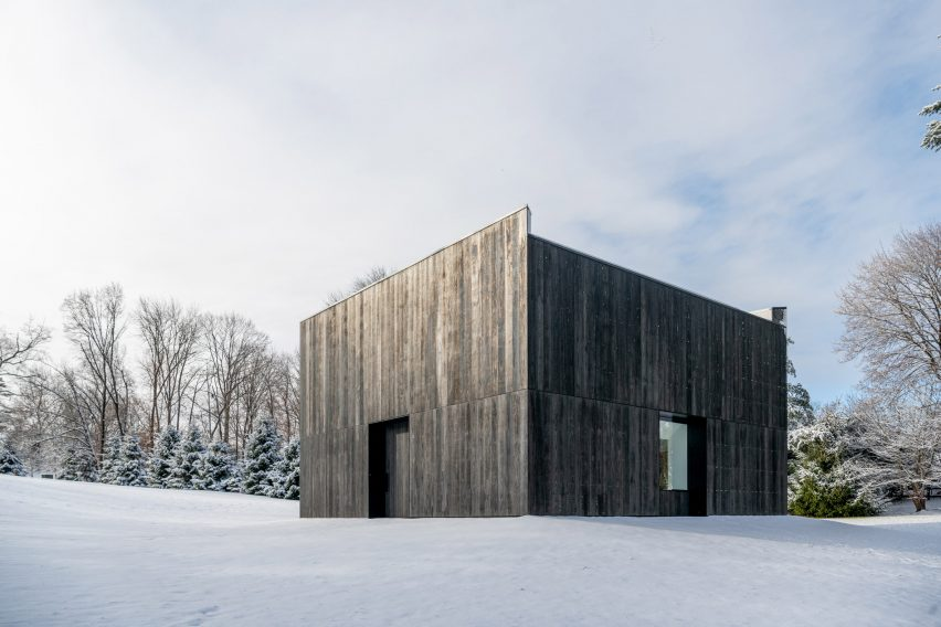 Snow surrounds charred-wood clad pavilion by OLI Architecture