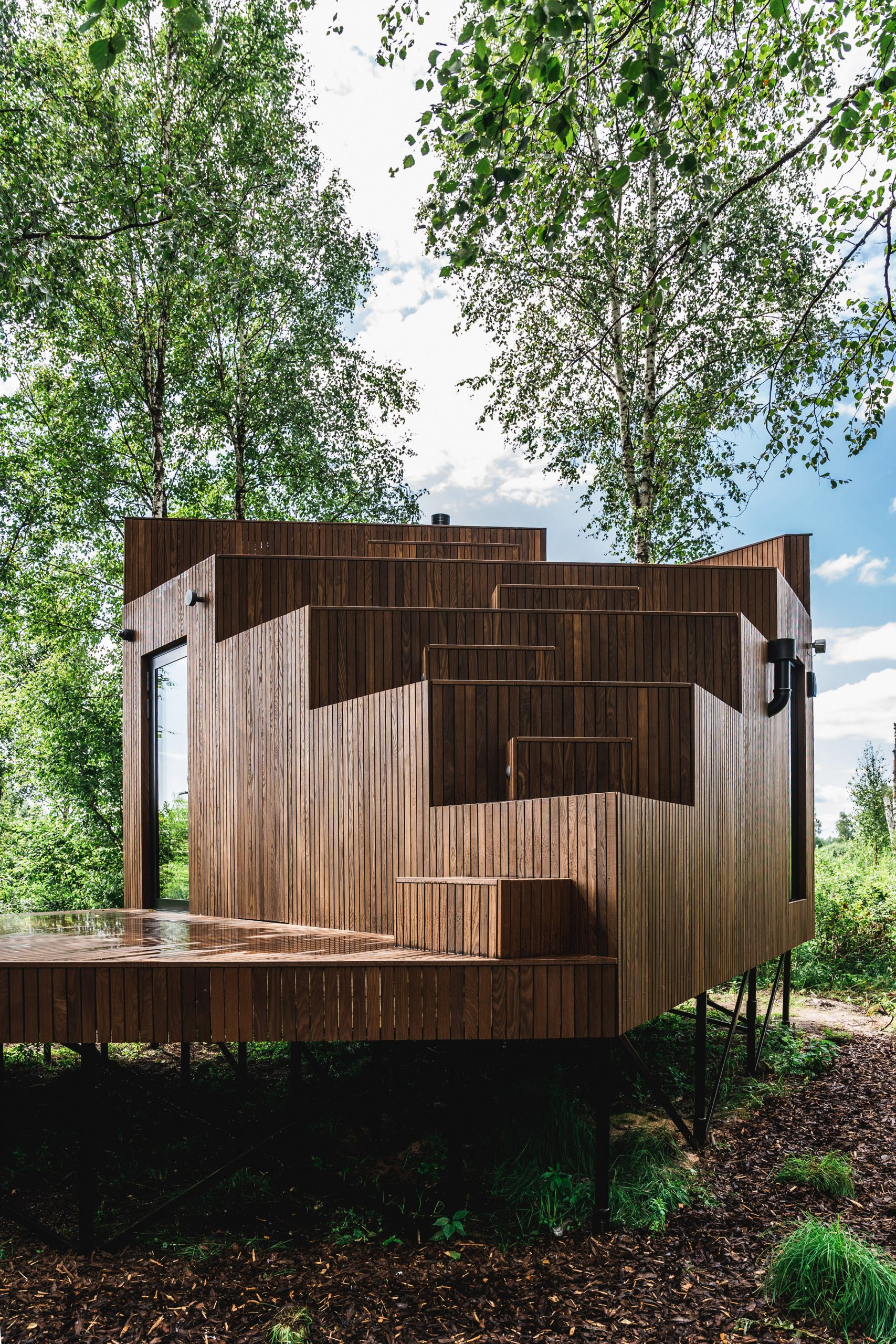 A stilted wooden cabin with a stepped facade