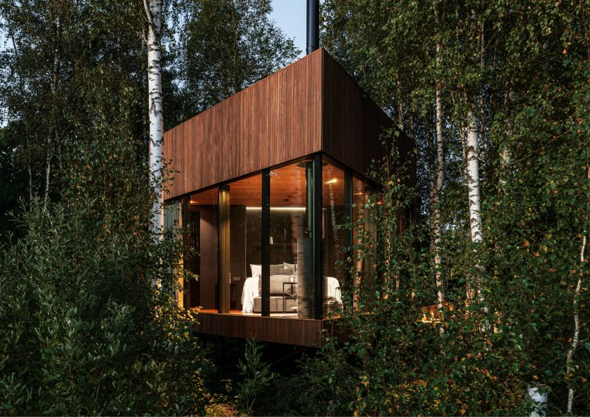 A glass and wood cabin in woodland