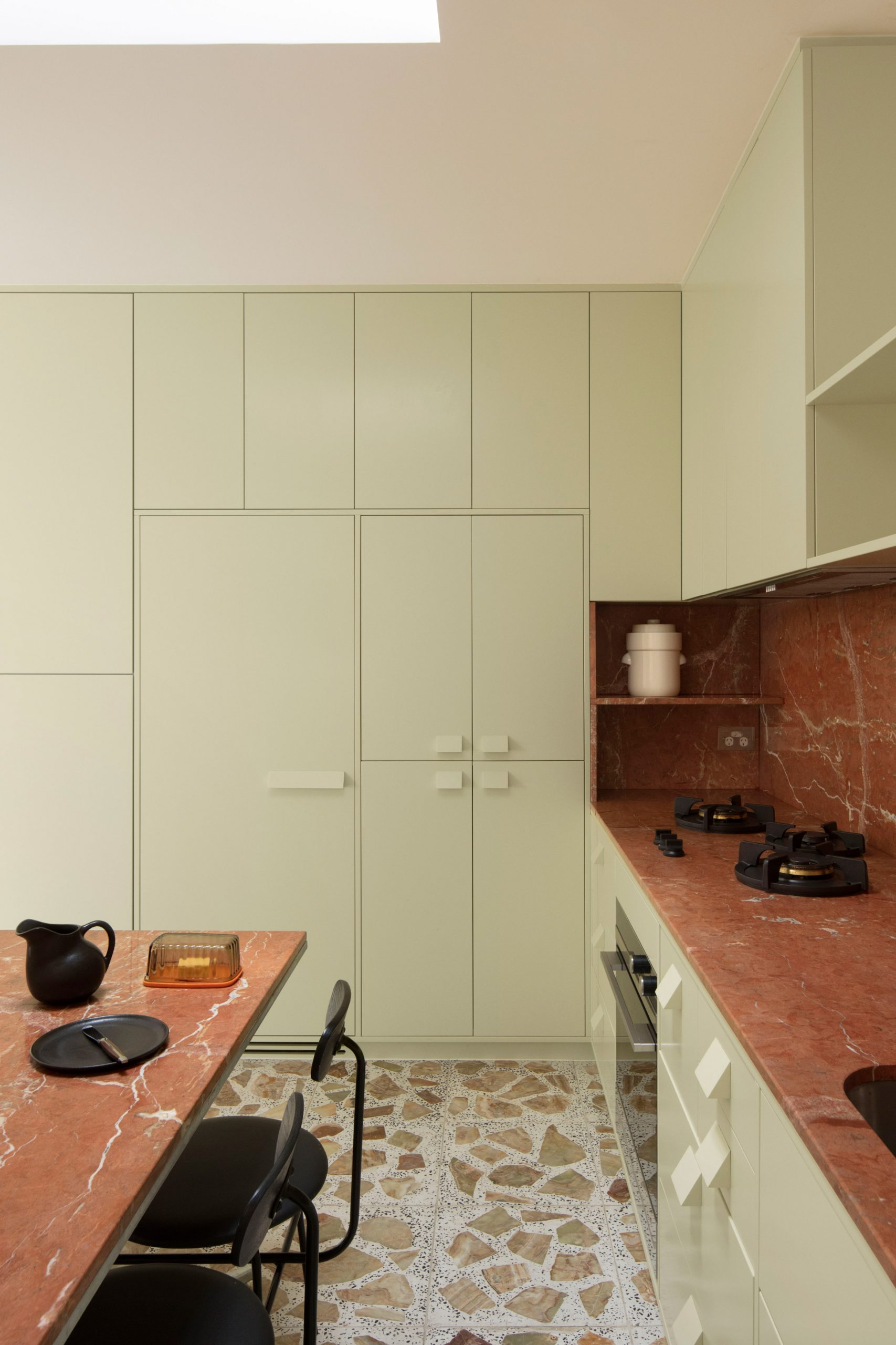 Pistachio green cabinets and red marble worktops in Brunswick apartment by Murray Barker and Esther Stewart