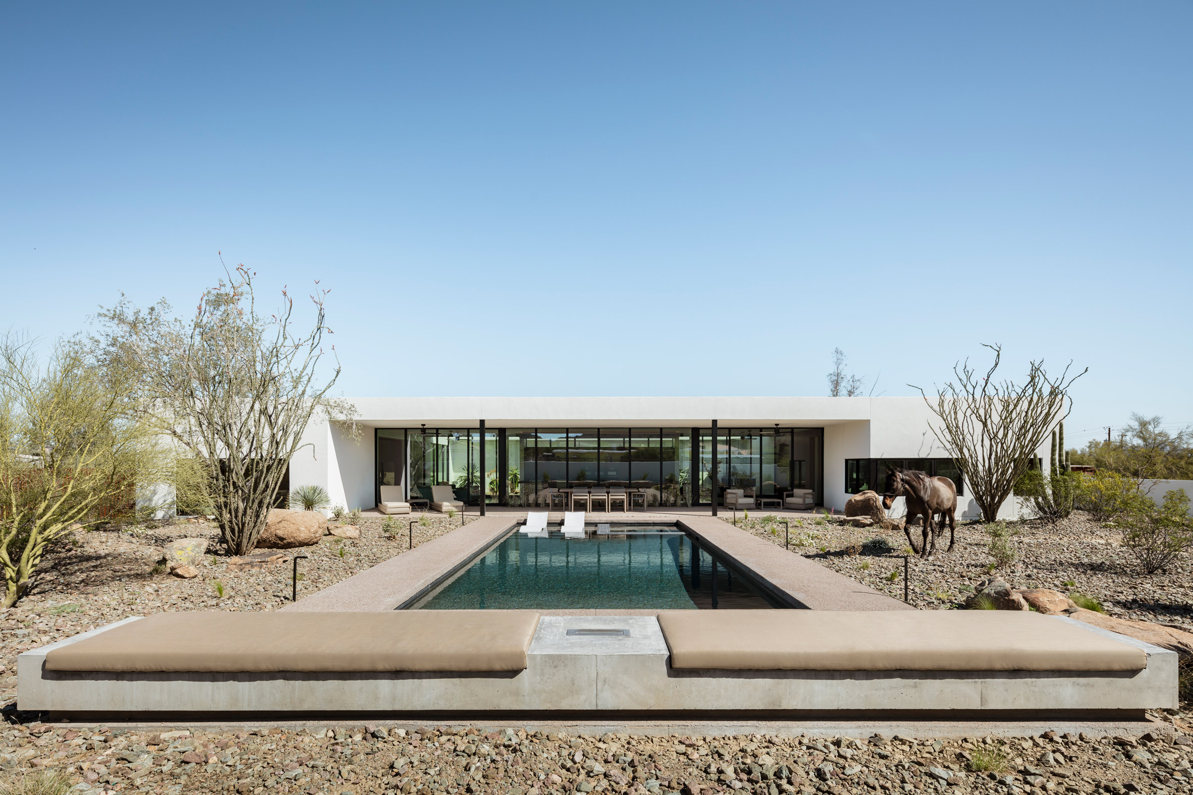 Concrete bench and firepit overlooking a swimming pool