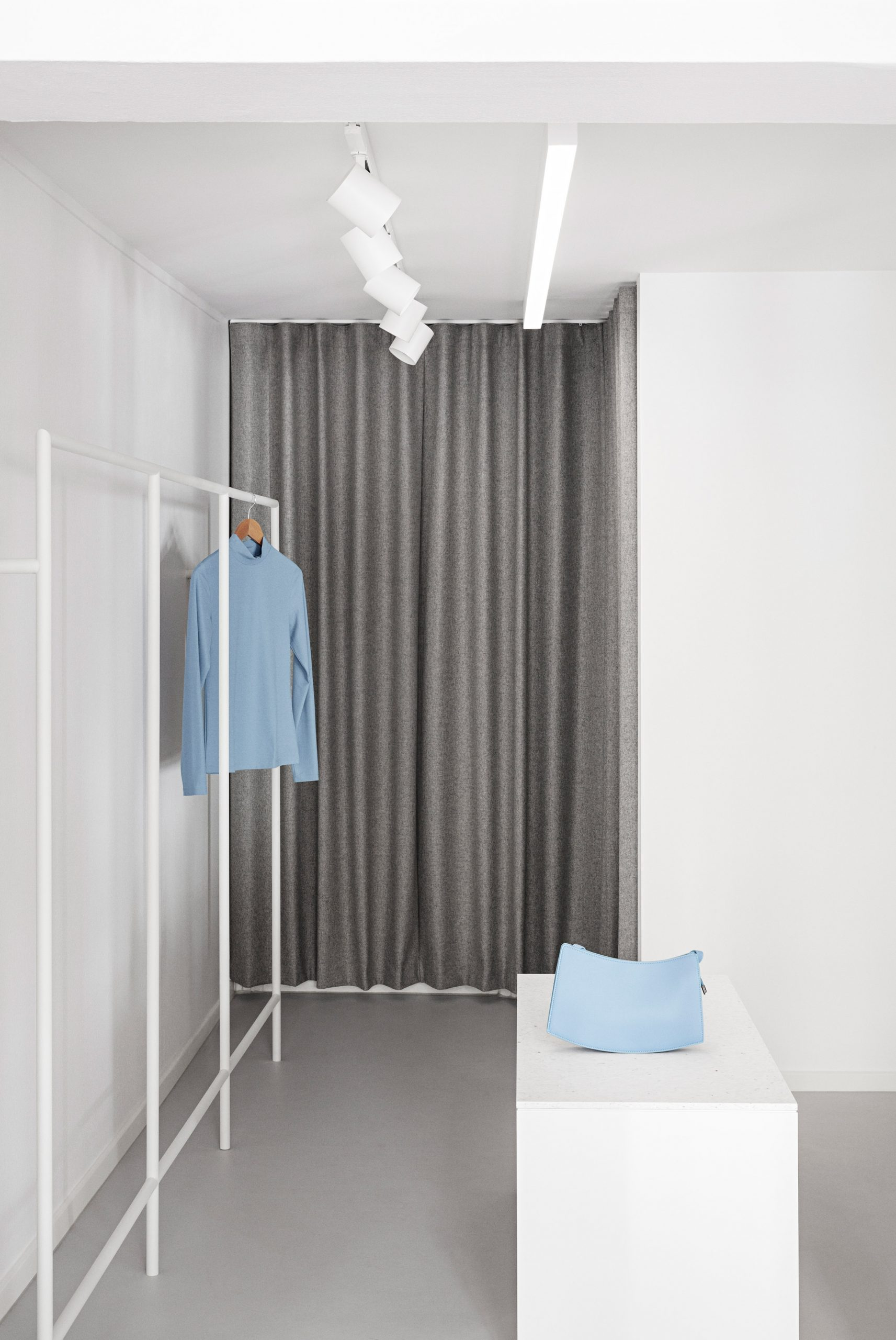 Grey wool changing room curtains and white rails in the OCE Copenhagen store interior