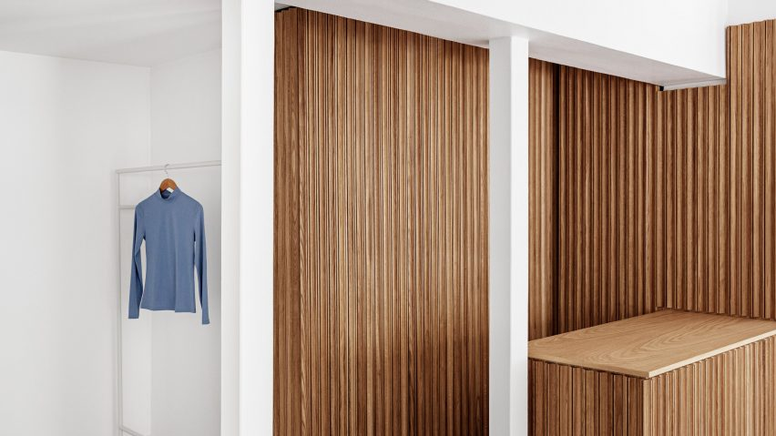 Wooden counter and white clothing rails in the OCE Copenhagen store interior by Aspekt Office