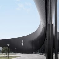 A curved black facade of a car factory