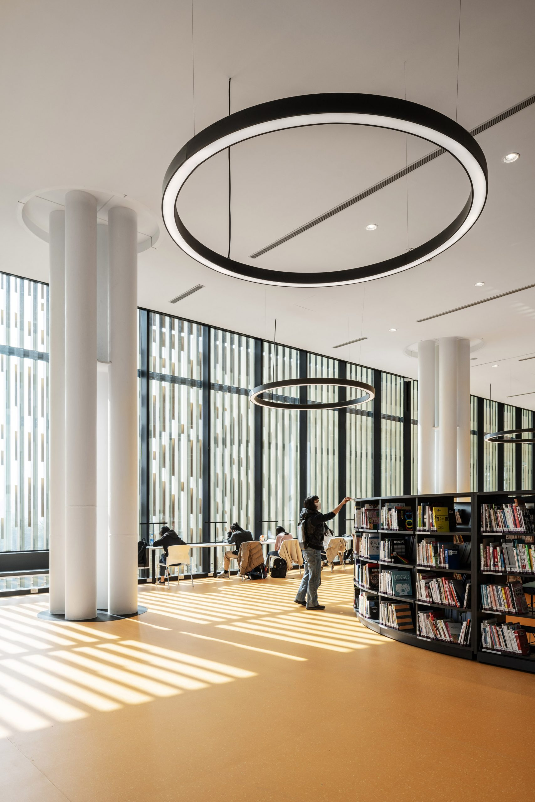 A double-height library with a bright yellow floor