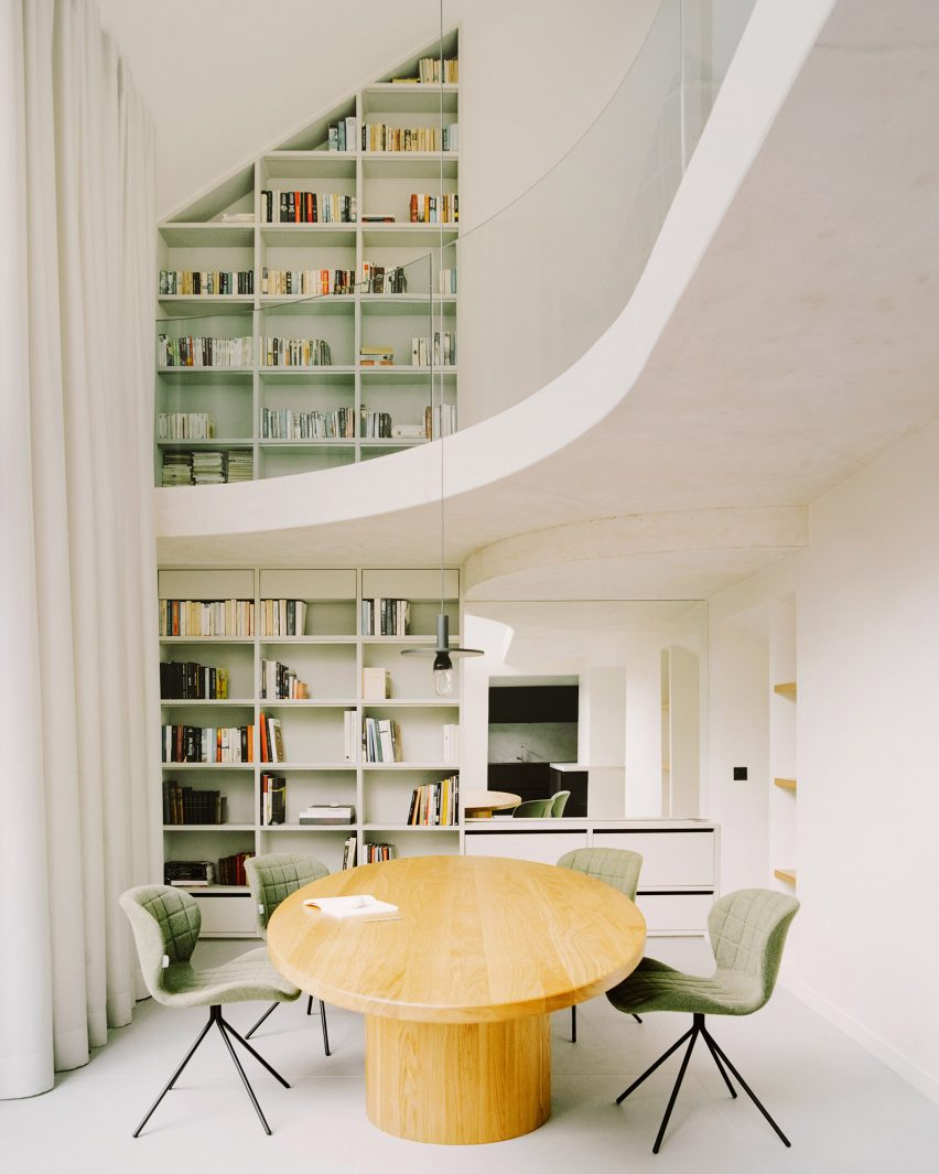 A white-walled double-height dining room in a Parisian townhouse