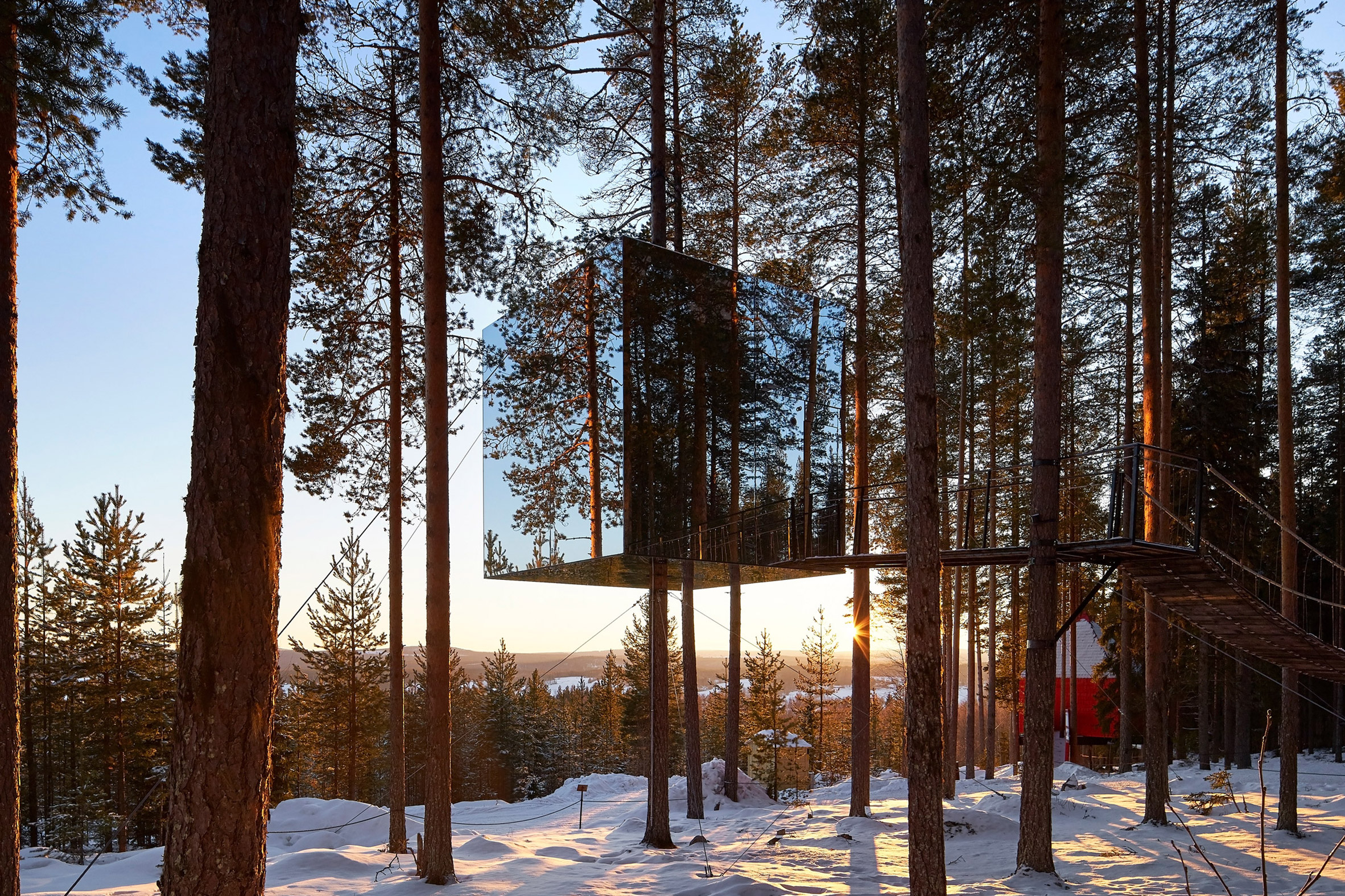 Mirrored cabin perched above ground blends with the sky and trees